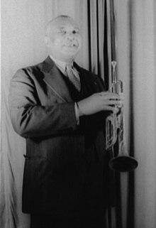 Short-haired African American man wearing a black suit and tie and holding a trumpet, standing facing the camera and smiling.