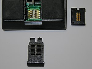 ROM cartridge - TI59 calculator with ROM software library module at right, showing gold-plated contacts.