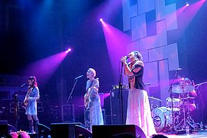 Four female musicians performing live on-stage against a black and white backdrop with violet lights.