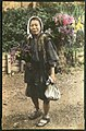 Woman with flowers in a basket on her back, Japan. (10797873364).jpg