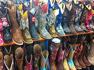 Cowboy boot - Women's boots on a display rack. Many boots for both sexes are highly decorated.