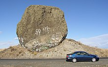 This photo shows an automobile passing in front of a rock which is essentially fully exposed. The rock has a rough, dark surface indicating it is weathered basalt and is roughly circular in exposed cross-section. The rock is immediately adjacent to a roadway – the road cut removed much of the earth from one side of it exposing it – from the excavation it is evident that the rock sits on a mound of glacial till. The rock is approximately 2 times the length of the car (i.e., ~ 9 meters) in one direction and 5 times the height of the car in the other direction (i.e., ~ 9 meters). Since the rock has not tipped onto the road and no structural support is provided, it must be approximately as deep as it is wide and high. Since the density of basalt is 3 grams per cubic centimeter, this puts the mass of the rock at about 400 to 500 metric tons (consistent with the references).