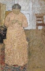 Femme en rose tricotant
