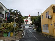 Photographie de la rue de l'église de Deshaies avec l'église en arrière-plan.