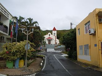 "Death in Paradise (TV series) - Deshaies' church is right next to the fictional ""Honoré police station""."