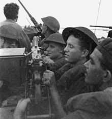 Black and white photo showing men in military uniforms wearing helmets in a very crowded vehicle. The men are pushed up against a large machine gun, and another machine gun is visible at the front of the vehicle pointing at the sky.