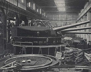 A large turret with three guns being assembled in a factory.