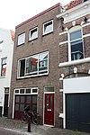 Huis met 19e-eeuwse bepleisterde lijstgevel. Fraaie kap. Nok evenwijdig aan de straat. Dakkapel. Getoogde vensters