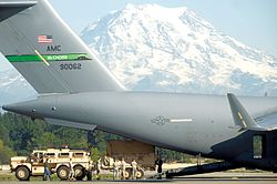 A C-17A Globemaster III of the 62nd Airlift Wing loading army personnel at Joint Base Lewis-McChord, with Mount Rainier in the background.