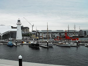 Australian National Maritime Museum - Some of the small vessels on display at the Australian National Maritime Museum. Foreground (left to right): refugee vessel Tu Do, racing yacht Akarana (without masts), pearling lugger John Lewis, ketch Kathleen Gillett, naval officer's launch MB 172, and a museum workboat. In the background are the lightvessel Carpenteria, the barque James Craig, and the original Cape Bowling Green Lighthouse.
