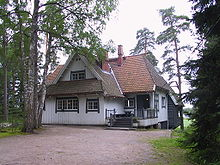 A white house of north European appearance with an orange tiled roof, surrounded by trees