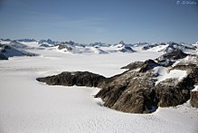 A distance shot near Juneau, Alaska. The area is covered in untouched white snow with mountain peaks in the distance. To the right of the image, nearer the photographer, is an uncovered outcrop of rocks.