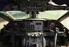 L'interno di un G-222 dove si può notare che malgrado il velivolo sia bimotore sono presenti quattro manette all'estrema destra ed estrema sinistra della console centrale che sono quelle della spinta dei motori.