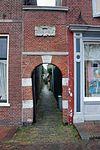 foto van Eenvoudig rondboogpoortje, toegang gevend tot de krom elleboogsteeg, met natuurstenen blokken in de posten en een als sluitsteen