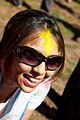 An Indian mother smiles as her child applies holi color to her.jpg