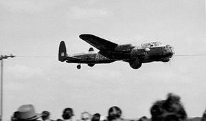 The Dam Busters (film) - An Avro Lancaster B.VII modified for the film with cut-out bomb bay and mock bouncing bomb demonstrating to a crowd at Coventry Airport in 1954