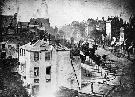 View of the Boulevard du Temple, taken by Daguerre in 1838 in Paris, includes the earliest known photograph of a person. The image shows a busy street, but because the exposure had to continue for several minutes the moving traffic is not visible. At the lower right, however, a man apparently having his boots polished, and the bootblack polishing them, were motionless enough for their images to be captured. Boulevard du Temple by Daguerre (unmirrored).jpg