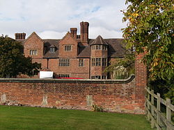 A photograph of a large, three-storey brick house, set well back behind a garden wall.