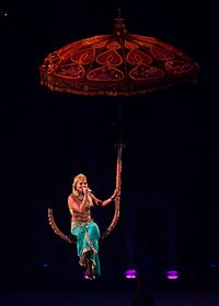 A female blonde performer. She is singing while suspended on a giant umbrella in the air. She wears eastern-inspired clothes.