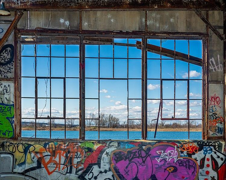 Окно в разрисованном граффити здании заброшенного аэродрома Флойд Беннет Филд[en] в Бруклине, Нью-Йорк