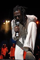 A man on a stage in white clothing, holding a microphone and bending over. In the background are women standing behind microphones.