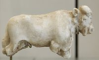 A carved, white statue of a bull missing its legs and with a head showing details of ears, mouth, nose, and eyes