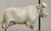 Резная белая статуя быка без ног с изображением ушей, рта, носа и глаз на голове.