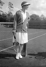 A woman looking away from the camera with a tennis racket in her right hand and a colored sweater on and all white clothing, which this picture is a black and white