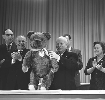 Khrushchev (holding the teddy bear) on his visit to East Germany with Nikolai Podgorny (clapping his hands) Bundesarchiv Bild 183-B0118-0010-027, Werk fur Fernsehelektronik, Besuch Chruschtschow.jpg