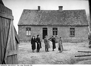 "Volksdeutsche Mittelstelle - German settlers are shown around their Nazi-appropriated farmhouse in occupied Poland in November 1939 during action ""Heim ins Reich"""