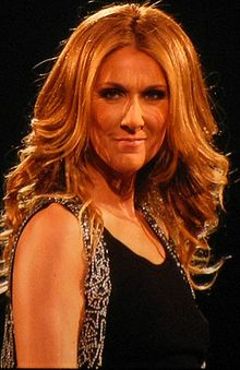 A woman with curly blonde hair wearing a black dress.
