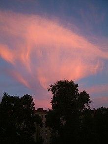 Изображение искаженного перистого облака, сияющего красным на закате.  Осенние полосы (похожие на длинные тонкие ленты) спускаются с облаков.