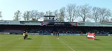 One of the stands of the Bootham Crescent association football ground, with supporters sitting down and players standing on a grass field below