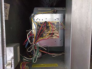 HVAC - The control circuit in a household HVAC installation. The wires connecting to the blue terminal block on the upper-right of the board lead to the thermostat. The fan enclosure is directly behind the board, and the filters can be seen at the top of the image. The safety interlock switch is at the bottom left.
