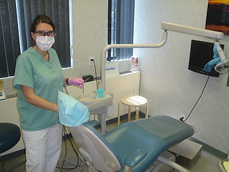 Dental hygienist - Dental hygienist holding a scaler