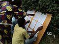 Des électeurs parcourent les listes électorales dans un centre de vote (Collège Alfajiri) à Bukavu 3 (6424786441).jpg