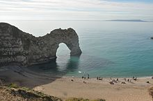 People on the beach show the scale of the arch. The Isle of Portland can be seen on the horizon. & Durdle Door - Wikipedia