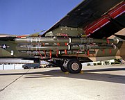 Closeup view of cylindrical bombs and ordnance carried under a mostly green aircraft wing