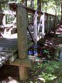 FLT M01 4.32 mi - Bridge over Wolf Run showing tel pole stringers sitting on tel pole cross sills, which sit on tel pole posts - panoramio.jpg
