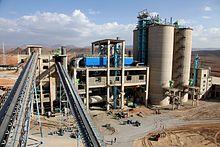 vue d'une usine avec deux convoyeurs au premier plan, un bâitment de type industriel et quatre silos à leur droite