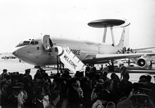 Black-and-white photograph with angled front view of four-engine jet aircraft on ramp with front fuselage door opened: A contingent of people are there to welcome the jet, which has a disc-shaped radar perching on top of struts on the dorsal fuselage.