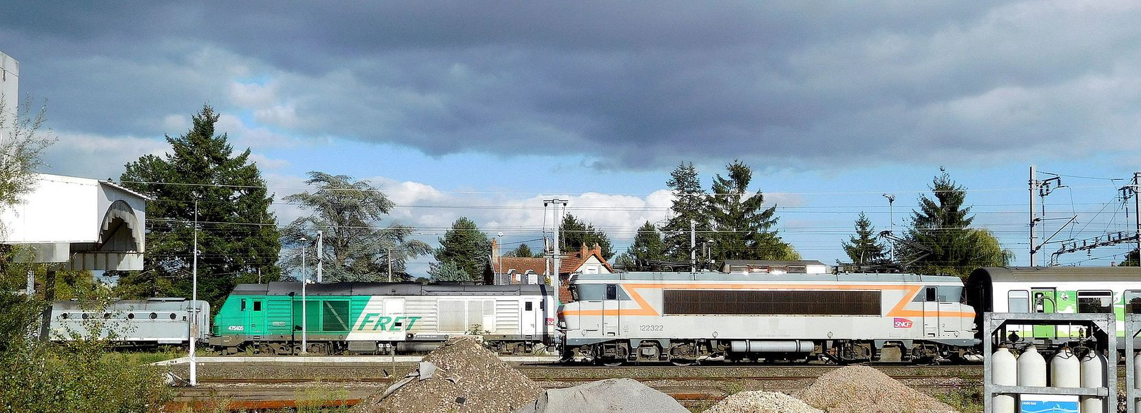 French rail vehicles on three different tracks (left to right):   preserved SNCF C 886 boiler van (at rest on a depot);  SNCF BB 475405 diesel electric locomotive (for freight, at rest on a canton) and wagons (not visible);  SNCF BB 122322 electric locomotive (just left the station of Cosne-sur-Loire, goes to Paris) and passenger cars (only one visible).