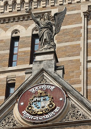 Municipal Corporation Building, Mumbai - Winged allegorical figure representing the 'urbs prima in Indis' and the Coat of Arms of Bombay below