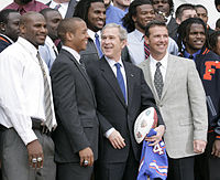 Photo depicts a smiling Chris Leak, quarterback of the Florida Gators, together with his Florida Gators football teammates, coach Urban Meyer, and U.S. President George W. Bush, who is holding a Gators football jersey and commemorative football.