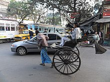 A congested intersection showing different vehicles such as a hand-pulled rickshaw, taxis, tram and car