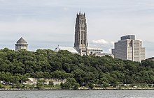 A landscape of Riverside Park; behind the park's trees is the tower of Riverside Church, at center