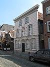 foto van Huis met schilddak en gebosseerd grijsgepleisterde lijstgevel, vensters met stucversiering; nog geheel woonhuisvorm