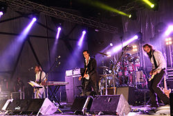 A rock band performing live on-stage. The stage is brightly lit On the left, a man plays bass behind a keyboard. In the centre, a man plays guitar and behind him a man plays drums. On the right, a man plays an electric mandolin.