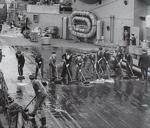 Black-and-white photograph of sailors scrubbing a ship's deck