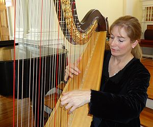 Pedal harp - Harpist Elaine Christy plays with both hands approaching the strings from either side of the harp; foot pedals (not shown) can change the pitch of specific strings by a half step.